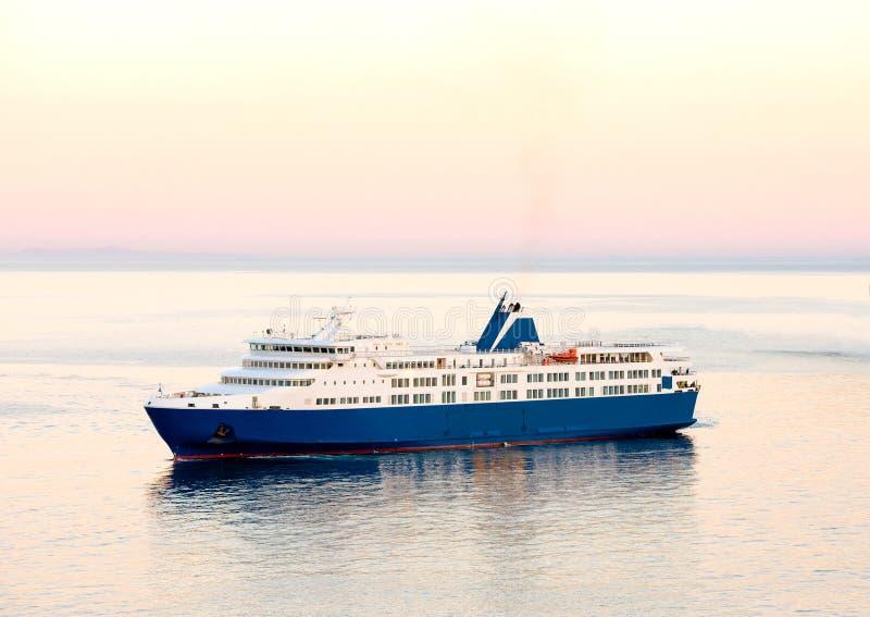 日落和蓝色白色渡轮在希腊海岛 免版税库存照片