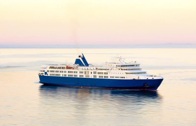 日落和蓝色白色渡轮在希腊海岛 免版税图库摄影