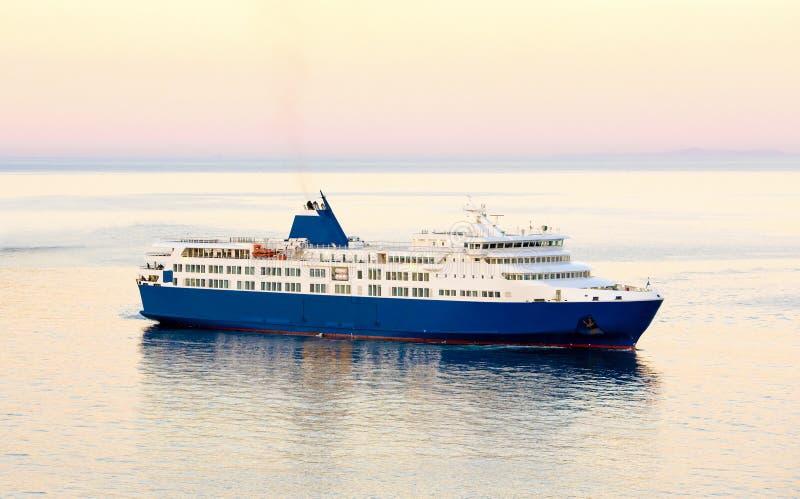 日落和蓝色白色渡轮在希腊海岛 库存图片