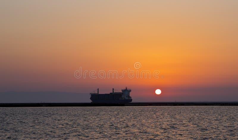 日落和集装箱船 库存照片