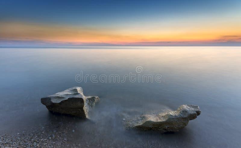 日落和tworocks在柔滑的水中 图库摄影