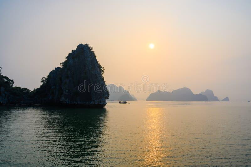 日落在下龙湾,越南 在有薄雾的岩层后的日落,在前景,反射的小船在南海,越南 免版税库存照片