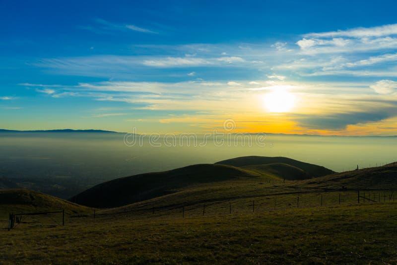 日落在云彩下的谷视图在山 图库摄影