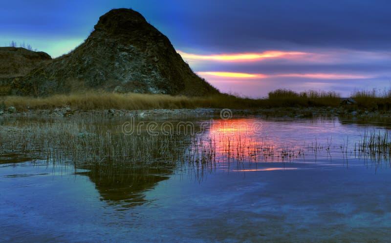 日落在冰冷的湖的晚秋天 免版税图库摄影
