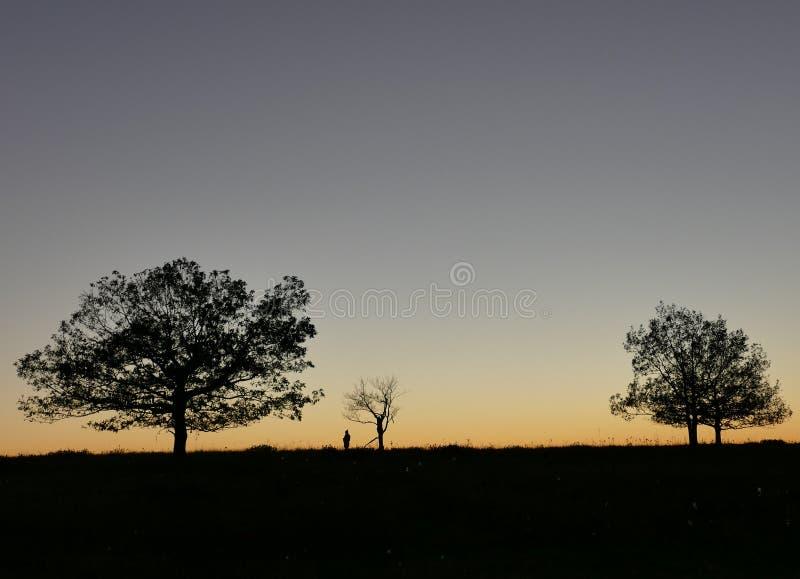 日落在有人的图silhouet的雪伦多亚  库存照片