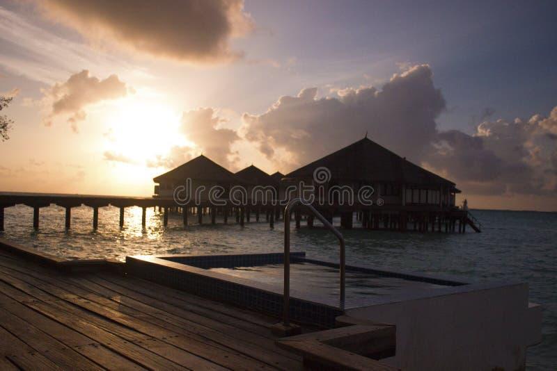 日落在有游泳池和海滩的马尔代夫 库存图片