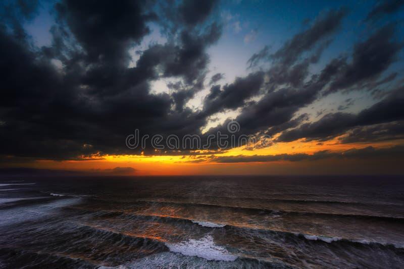 日落在有风大浪急的海面的海 免版税图库摄影