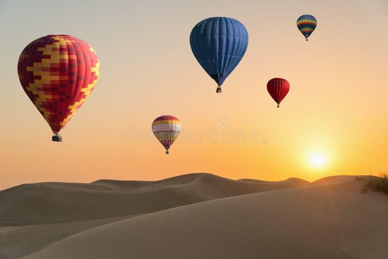 日落在沙漠,在天空的热空气气球 库存图片