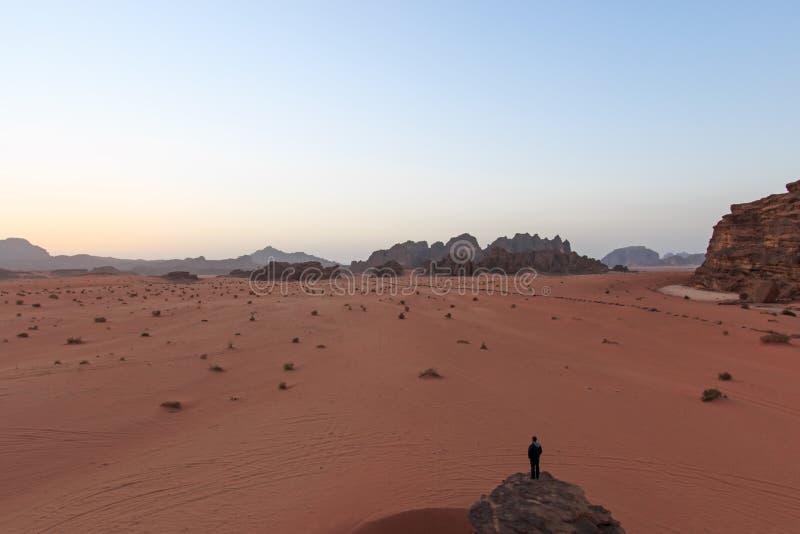 日落在瓦地伦沙漠,约旦,当一个人观看从一个岩石的场面在前景 库存图片