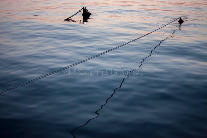日落在的里雅斯特港口在水中漂浮 库存图片
