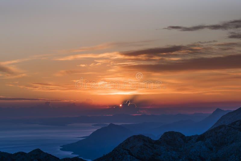 日落在Biokovo有有趣的光亮云彩、达尔马希亚海岸和山的自然公园在蓝色, Sveti Jure树荫下  免版税图库摄影