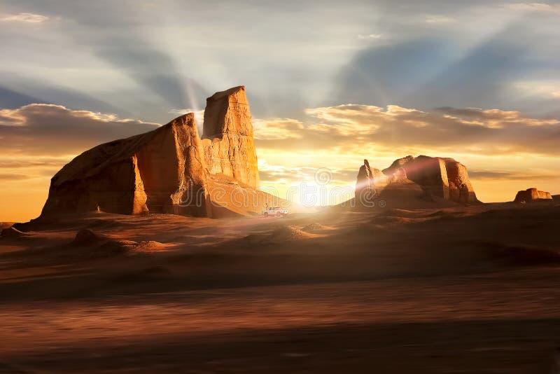 日落在Dasht-e Lut沙漠 在岩石下的美好的光芒 伊朗 克尔曼 库存照片