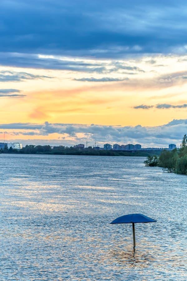 日落城市池塘和遮光罩在水中 库存图片
