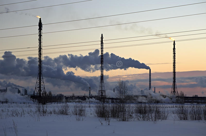 日落天空背景的精炼厂 冷淡的多雪的冬天晚上 图库摄影