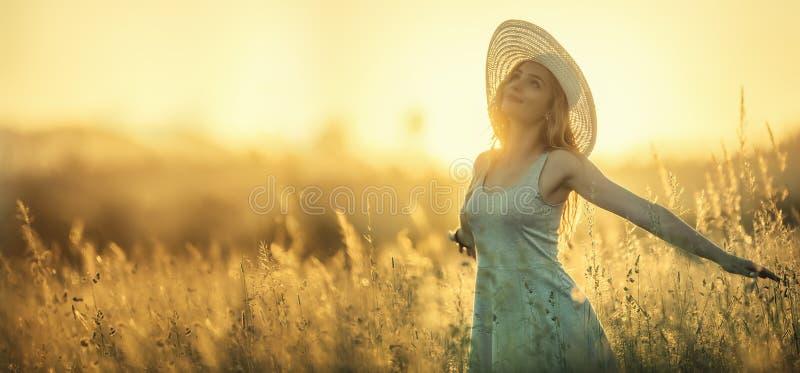 日落或日出的愉快的年轻女人在夏天自然用开放手 免版税图库摄影