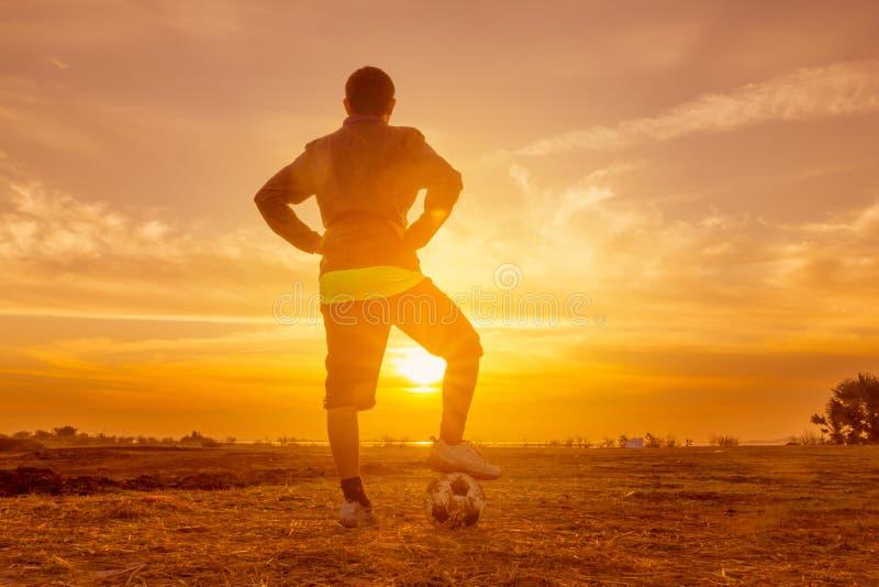 日落或日出背景的足球运动员 库存图片