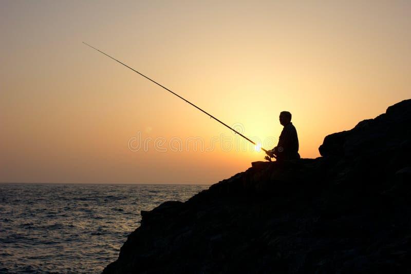 日落捕鱼的钓鱼者 免版税库存图片