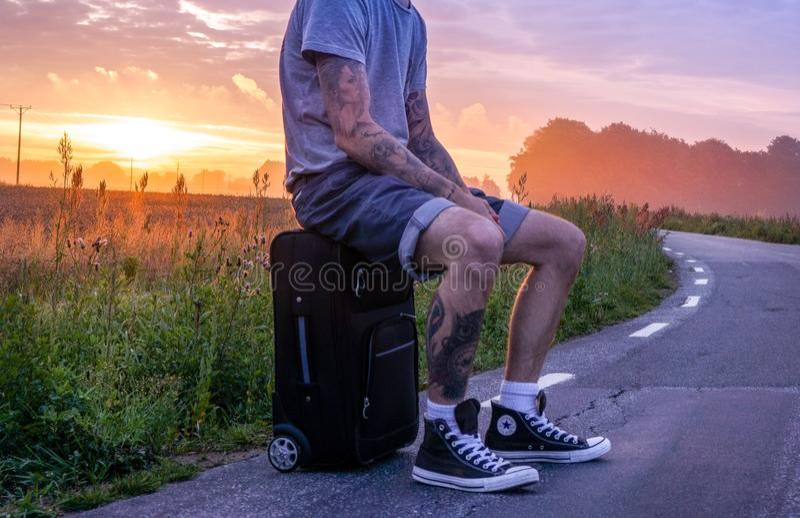日落时候,男子坐在路边行李上 免版税库存图片