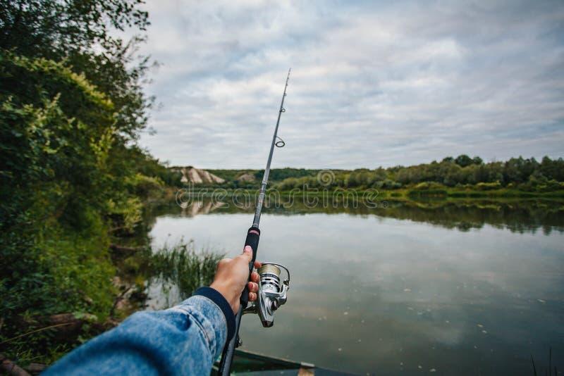 日落时在湖上钓鱼 手持卷轴的钓竿 免版税库存图片