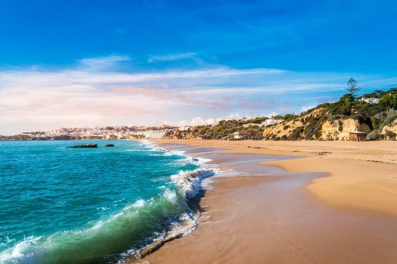 日落时,波涛在葡萄牙阿尔加韦阿尔布费拉度假村的沙滩上汹涌 免版税库存图片