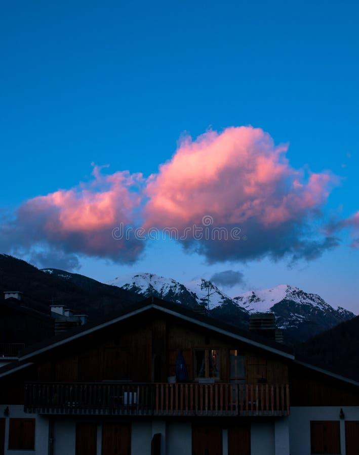 日落有桃红色的山房子多云在森林里 免版税库存照片