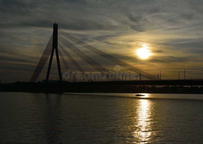 日落桥梁和小船 免版税库存照片