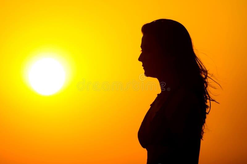 日落注意的妇女 库存图片