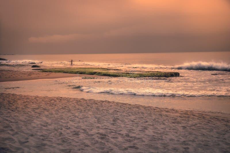 日落海滩海洋海浪波浪与剧烈的橙色日落天空和渔夫的风景风景 库存图片