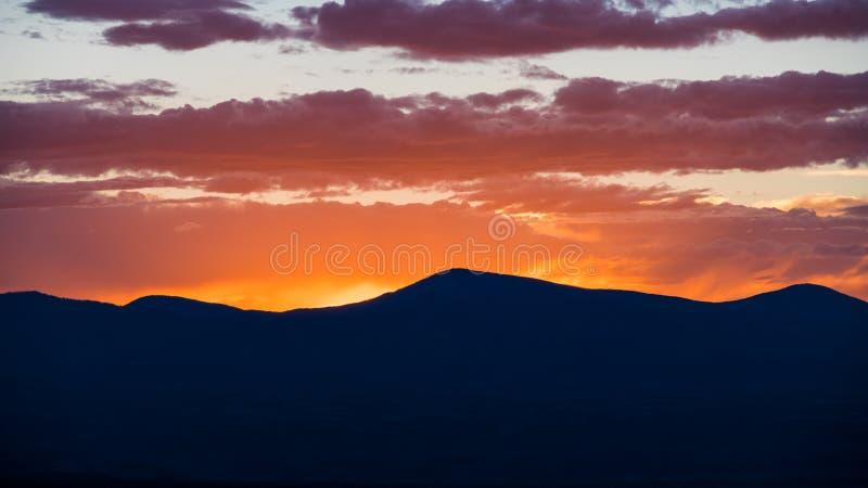 日落现出轮廓山脉并且上色天空和云彩在黄色,橙色,紫色和桃红色 库存图片