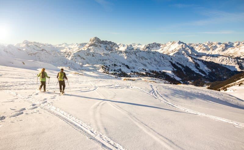 日落的两个雪靴远足者在高山冬天山 巴伐利亚德国 免版税库存照片