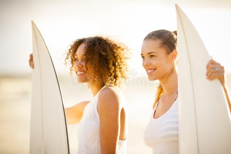 日落的两位女孩冲浪者 库存照片