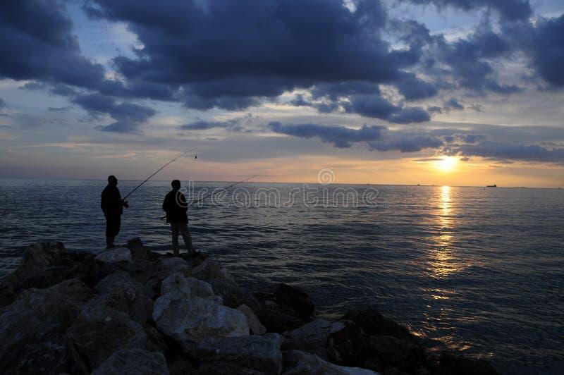 日落的两位渔夫 库存照片