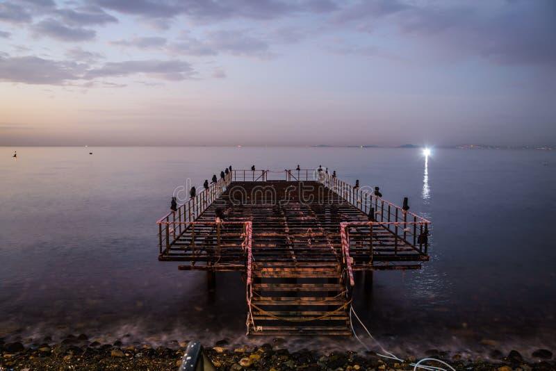 日落的使荒凉的船坞与风平浪静 库存图片