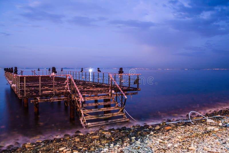 日落的使荒凉的船坞与风平浪静 免版税库存图片