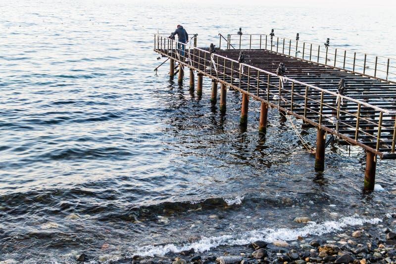 日落的使荒凉的船坞与风平浪静 库存照片