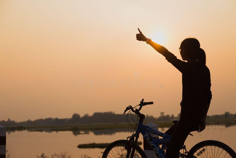 日落的剪影骑自行车的人女孩在草甸 库存照片