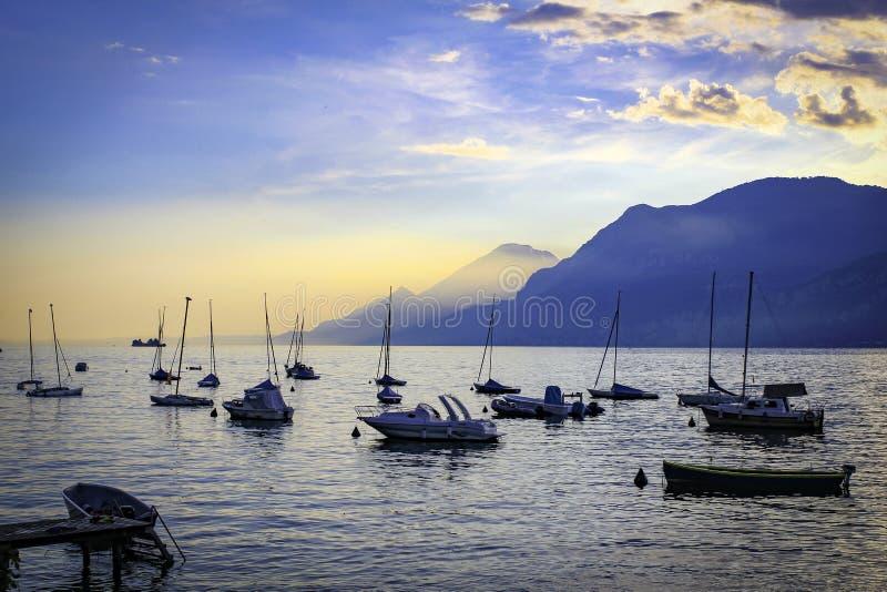 日落的加尔达湖港口与小船 库存照片