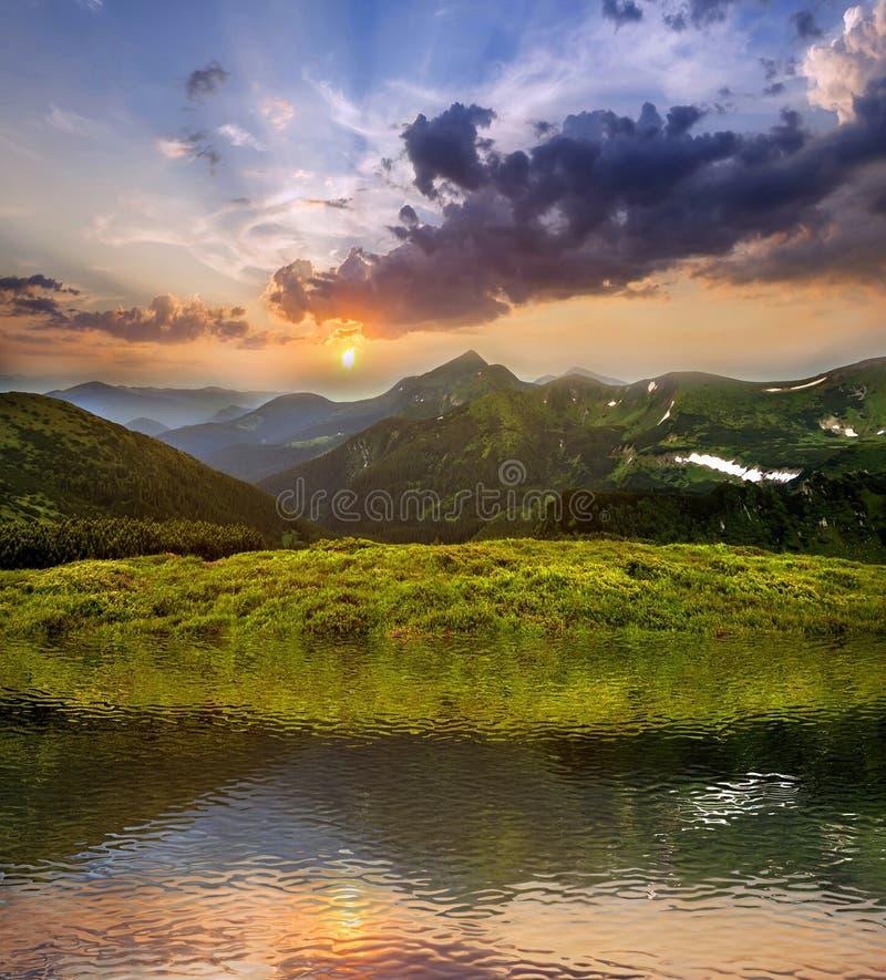 日落的山景城 绿色象草的谷全景,与雪补丁的木质的有雾的山峰,剧烈的多云天空和 图库摄影