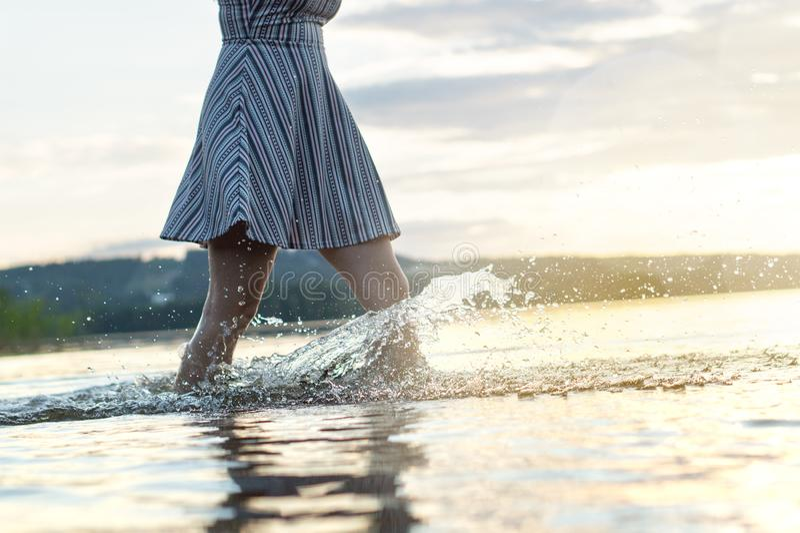 日落的年轻可爱的妇女 飞溅的水,当走时 库存照片