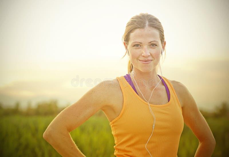 日落的微笑的女性慢跑者 免版税图库摄影