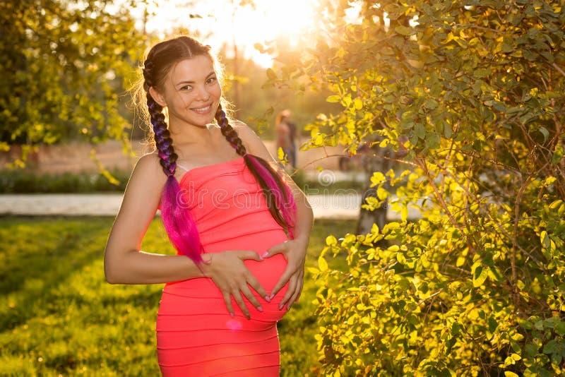 日落的怀孕的女孩在城市公园 图库摄影