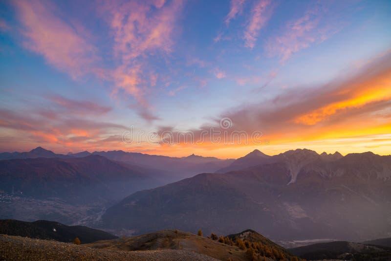 日落的意大利法国阿尔卑斯 在庄严山峰、干燥贫瘠地形和绿色山谷的五颜六色的天空 镶有钻石的旭日形首饰的a 库存照片
