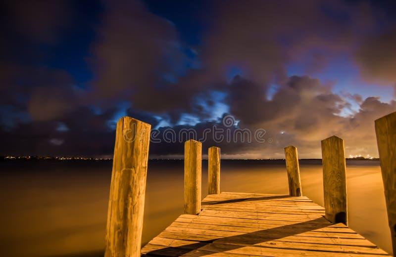 日落的木小船船坞与美丽的云彩 免版税库存图片