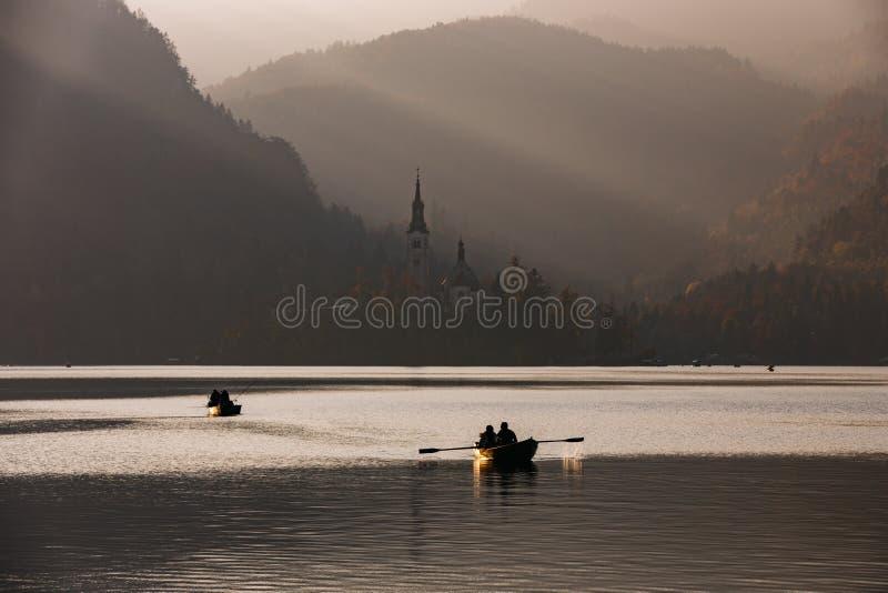 日落的流血的湖与小船 库存图片