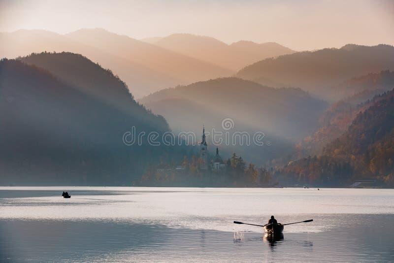 日落的流血的湖与小船 免版税库存图片