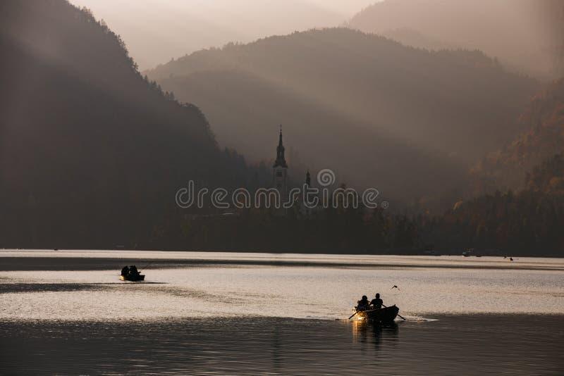 日落的流血的湖与小船 免版税库存照片