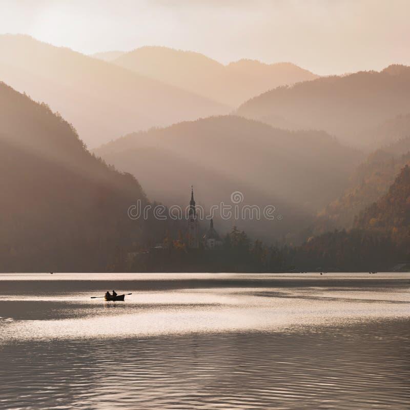 日落的流血的湖与小船 库存照片