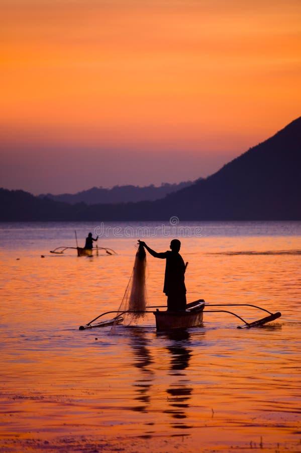 日落的渔夫在Taal湖,菲律宾 免版税库存图片