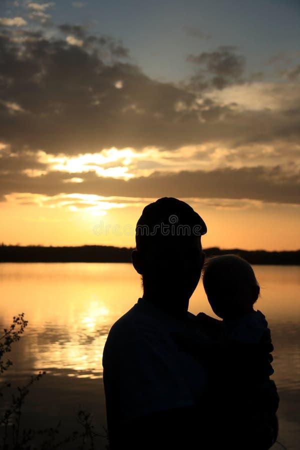 日落的父亲和女儿 免版税图库摄影