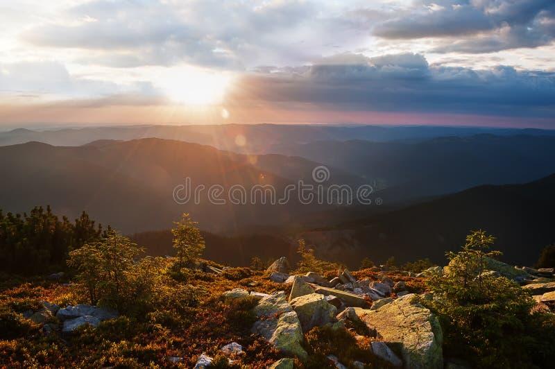 日落的看法从山的在距离 山的峰顶的黑暗的剪影,青苔gro巨大的块  库存图片